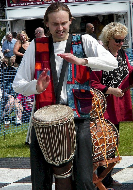 [ Malc playing djembe solo at Hertford Castle, photo by Tony ]