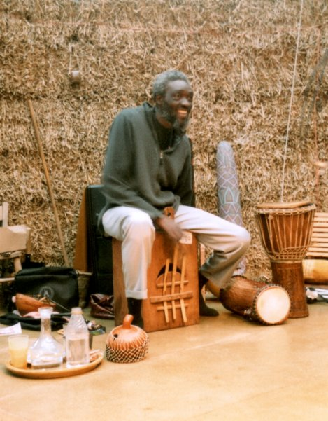 [ Ade Wallace singing and playing his large bass thumb piano in The Strawbale Studio ]